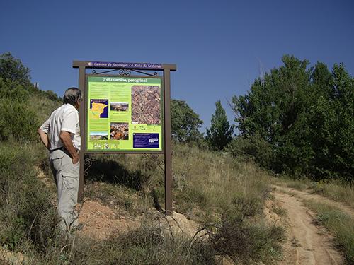 Un peregrino ante un cartel de la ruta El Camino de Santiago-Ruta de la Lana